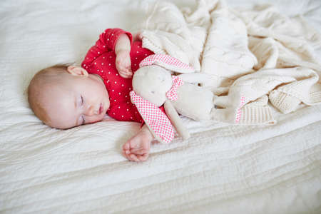 Baby girl sleeping under knitted blanket with her favorite toy. Little child in pink clothes having a day nap. Infant kid in nursery
