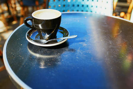 Cup of coffee on the table of traditional French street cafe in Paris, France
