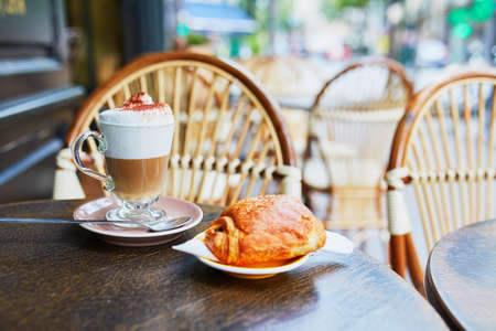 Cup of coffee and fresh pastry on the table of traditional French street cafe in Paris, France Banque d'images - 109827468
