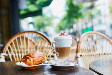 Cup of coffee and fresh pastry on the table of traditional French street cafe in Paris, France