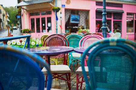 Colorful tables and chairs of empty French cafe