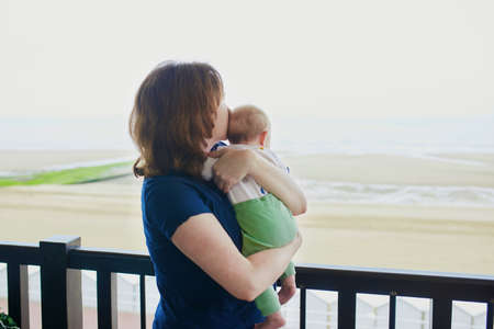 Mother and child on balcony of their home or hotel room. Woman holding baby girl in her arms and looking at the sea
