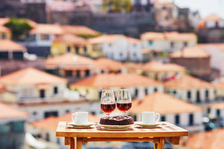 Two glasses of Madeira wine, two cups of fresh espresso coffee and traditional Portuguese honey and nut dessert bolo de mel in cafe with view to Funchal town, Madeira, Portugal Banco de Imagens - 110300748