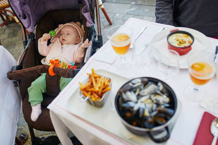Cheerful baby girl in stroller near table in restaurant. Going out with kids. Boiled mussels in white sauce with French fries and apple cider, traditional dish in Normany (France) or Belgium Banco de Imagens