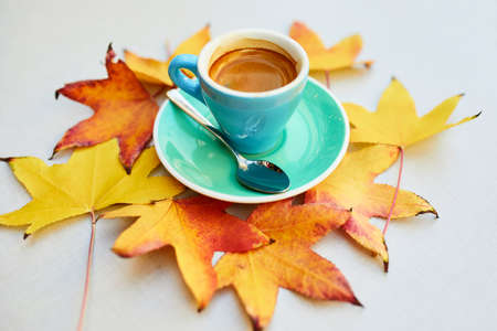Cup of fresh hot espresso coffee and autumn leaves on table of traditional Parisian outdoor cafe in Paris, France