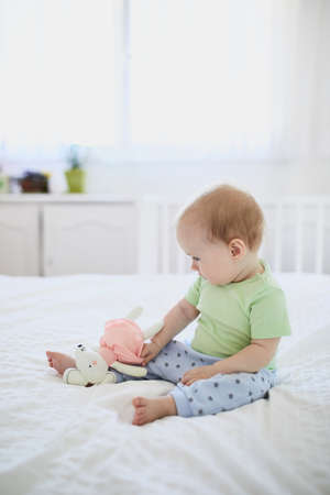 Baby girl sitting on bed and laughing. Happy healthy little child at home. Infant kid in sunny nursery