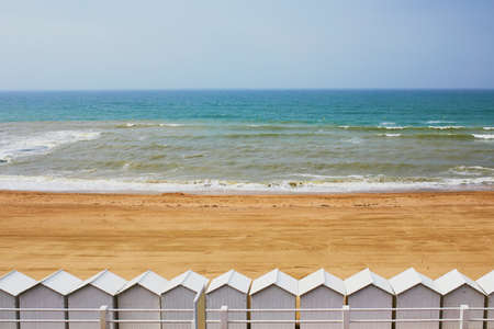 Row of white beach cabins on Atlantic coast in Normandy, France Stock Photo