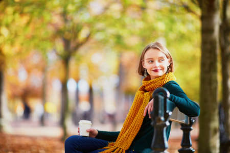 Happy young girl in yellow scarf with coffee to go walking in autumn park on a bright fall day Stok Fotoğraf
