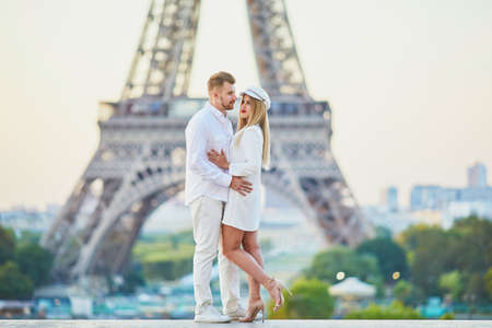 Romantic couple having a date near the Eiffel tower. Tourists in Paris enjoying the city