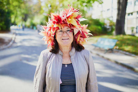 Happy middle aged woman in colorful maple leaves wreath walking in park on a sunny fall day