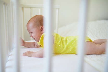 Adorable baby girl lying in co-sleeper crib attached to parents bed and crying. Little child not wanting day nap in cot. Infant kid in sunny nursery Stock Photo