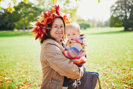 Happy middle aged woman wearing maple leaves wreath with baby girl on sunny fall day in park. Grandmother having fun with granddaughter outdoors. Autumn activities with kids 版權商用圖片