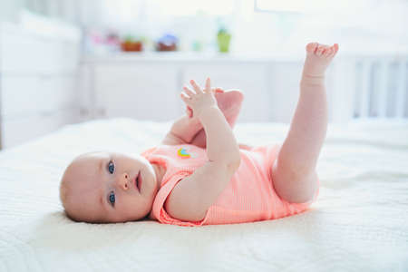Cute baby girl lying on her back and touching her feet. Happy healthy kid at home in nursery Reklamní fotografie