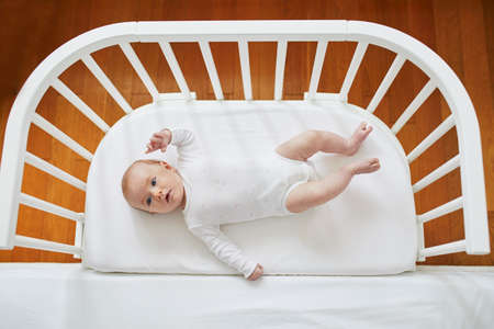Adorable baby girl in co-sleeper crib attached to parents bed. Little child having a day nap in cot. Infant kid in sunny nursery