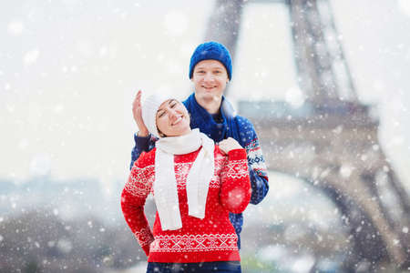 Happy couple near the Eiffel tower on a winter day under the falling snow. Trip to Paris during season holidays Stock Photo