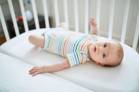 Adorable baby girl in co-sleeper crib attached to parents' bed. Little child having a day nap in cot. Infant kid in sunny nursery Stockfoto