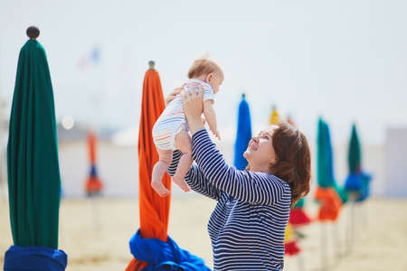 Mother and child on beach. Mom and baby girl having fun together in Deauville, Normandy, France