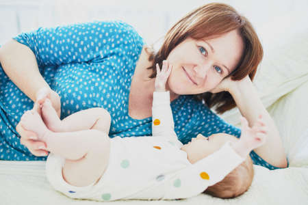 Mother and child in nursery. Mom and baby girl in bedroom. Parent and infant having time together and relaxing at home Stock Photo - 114464018