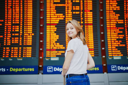 Young woman in international airport with luggage near flight information display Stok Fotoğraf