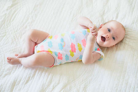 Adorable baby girl lying on bed and smiling. Happy healthy little child laughing. Infant kid in sunny nursery
