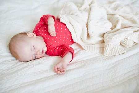 Baby girl sleeping under knitted blanket. Little child in pink clothes having a day nap. Infant kid in nursery