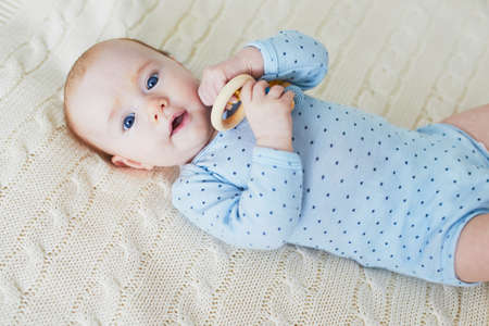 Adorable baby girl lying on bed with toy. Happy healthy little child laughing. Infant kid in sunny nursery