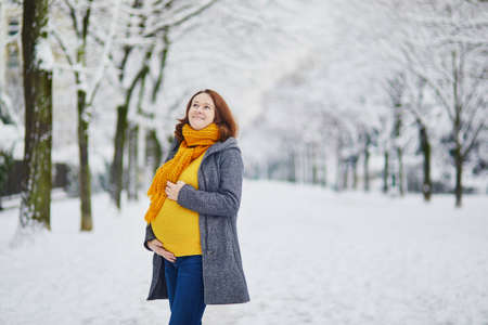 Beautiful pregnant woman on her last weeks of pregnancy walking in Paris on a day with heavy snow