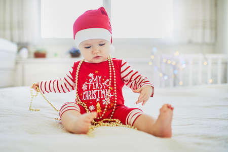 Happy little baby girl wearing pyjamas and Santa hat playing with New year tree decorations on her very first Christmas. Celebrating Xmas with kids at home