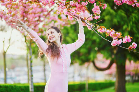 Happy young woman in pink dress enjoying cherry blossom season in Paris, France Фото со стока - 115798494