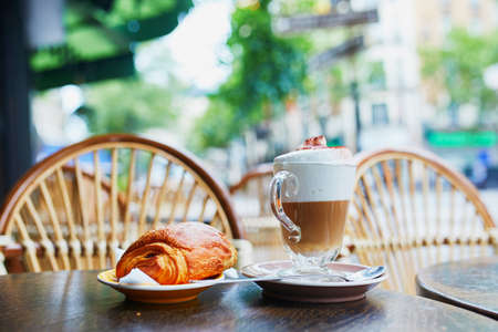 Cup of coffee and fresh pastry on the table of traditional French street cafe in Paris, France Banque d'images - 119791808
