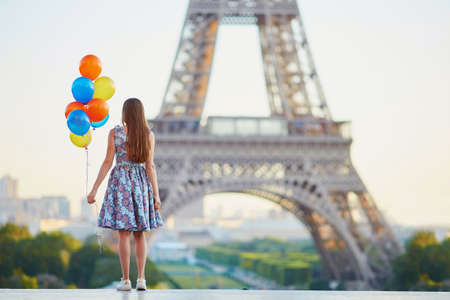 Romantic young woman in Paris with bunch of colorful balloons looking at the Eiffel tower Foto de archivo - 119791817