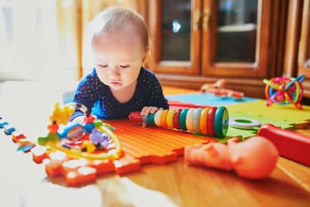 Baby girl playing with toys on the floor. Happy healthy little child at home