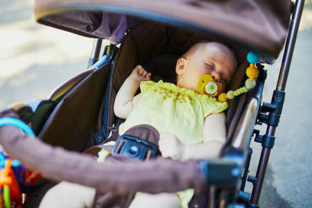 Baby girl sleeping in stroller. Little child in pram. Infant kid outdoors in pushchair Фото со стока