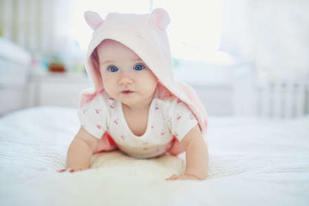 Adorable seven months baby girl relaxing in bedroom in pink clothes or towel with ears Stock Photo - 117719209