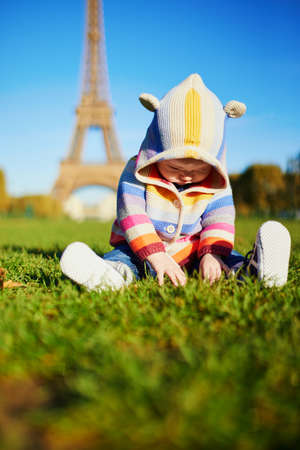 Adorable baby girl in warm knitted clothes sitting on the grass near the Eiffel tower in Paris, France