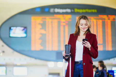 Young woman in international airport with luggage and coffee to go waiting for her flight
