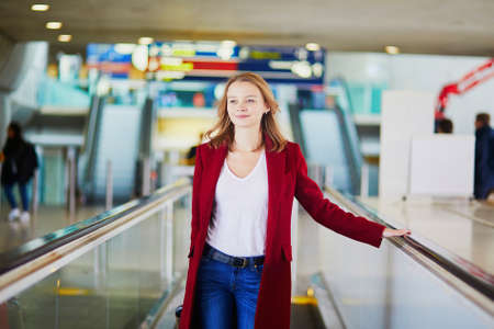 Young woman in international airport with luggage on travelator 免版税图像