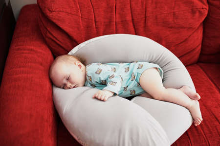 Cute adorable baby girl sleeping on breastfeeding pillow at home