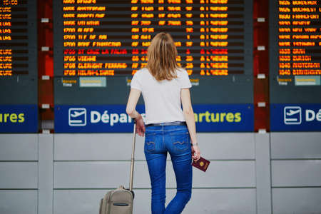 Young woman in international airport with luggage and passport near flight information display Stok Fotoğraf