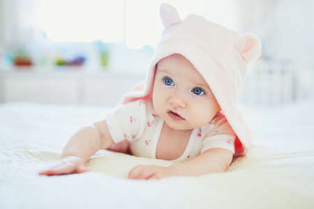 Adorable seven months baby girl relaxing in bedroom in pink clothes or towel with ears