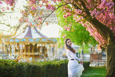 Happy young woman in white dress enjoying cherry blossom season in Paris, France