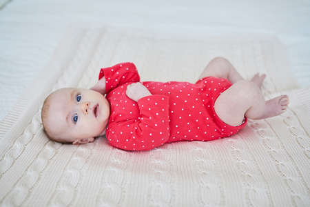 Adorable baby girl in pink bodysuit lying on bed. Happy healthy little child laughing. Infant kid in sunny nursery Stok Fotoğraf