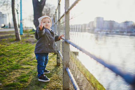 One year old girl standing next to metal fence in park and pointing with her finger. Toddler learning how to walk. Adorable kid walking in Paris, France
