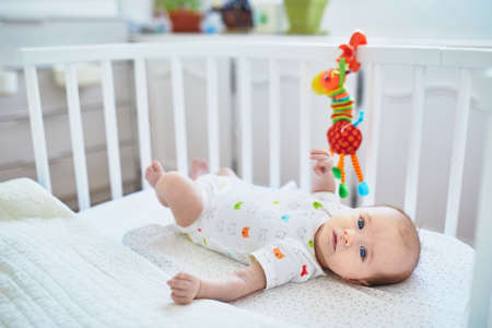 Adorable baby girl lying in the crib. Little child having a day nap in cot. Infant kid resting and playing with toys in nursery
