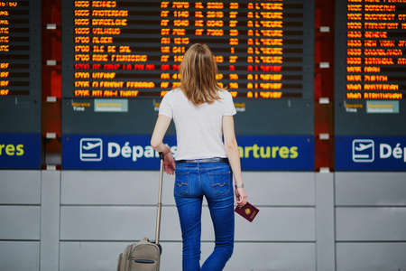 Young woman in international airport with luggage and passport near flight information display Stockfoto
