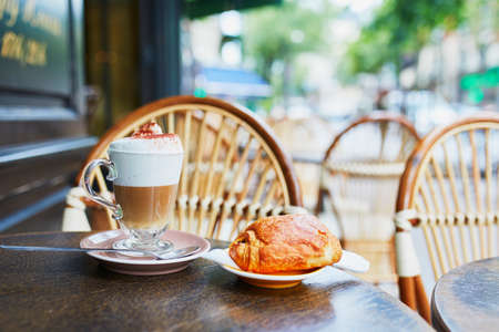 Cup of coffee and fresh pastry on the table of traditional French street cafe in Paris, France Banque d'images