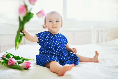 Baby girl in blue dress playing with bunch of pink tulips. Little child at home in sunny nursery. Toddler having fun with flowers