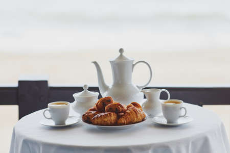 Two cups of coffee and traditional French pastry in cafe or restaraunt with a view. Breakfast on balcony near sea or ocean Banque d'images - 119372041