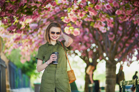 Beautiful French woman walking in Paris on a spring day at cherry blossom season 免版税图像