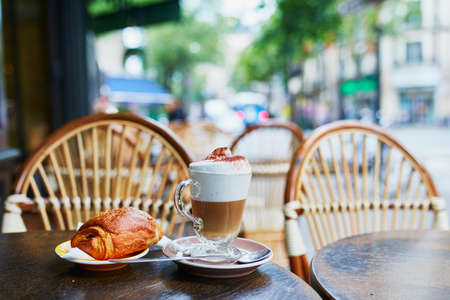 Cup of coffee and fresh pastry on the table of traditional French street cafe in Paris, France Banque d'images - 121286962
